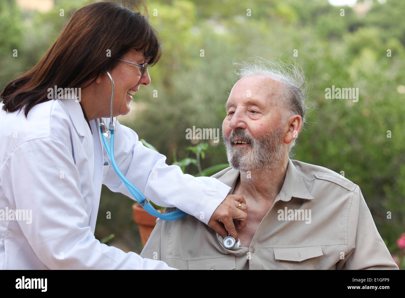 dr with stethoscope checking senior patients heart beat - Stock Image
