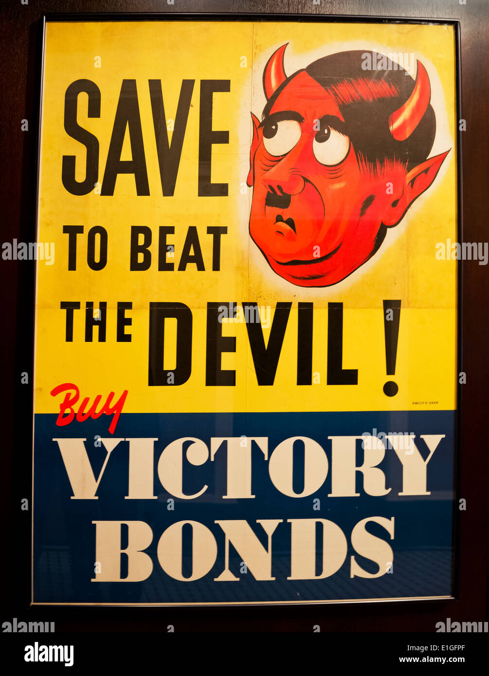 Canadian World War II poster:  'Save to Beat the Devil:  Buy Victory Bonds'. Featuring Hitler as the devil. - Stock Image