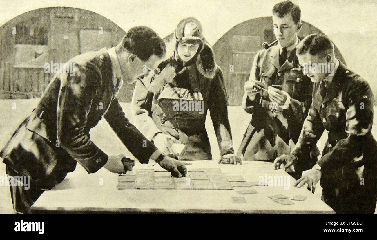 Photograph of pilots of the Royal Air Force piecing together a map for a night-bombing. Dated 1942 - Stock Image