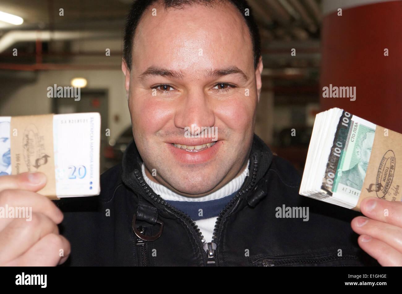 Portrait of European man holding wad on money - Stock Image