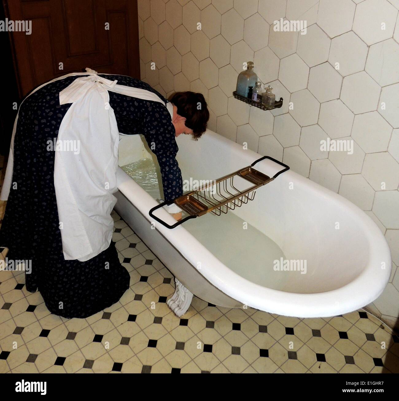 Victorian bath with butler pouring hot water in a tiled en-suite bathroom.  Decorated to 19th century requirements, Warwick - Stock Image