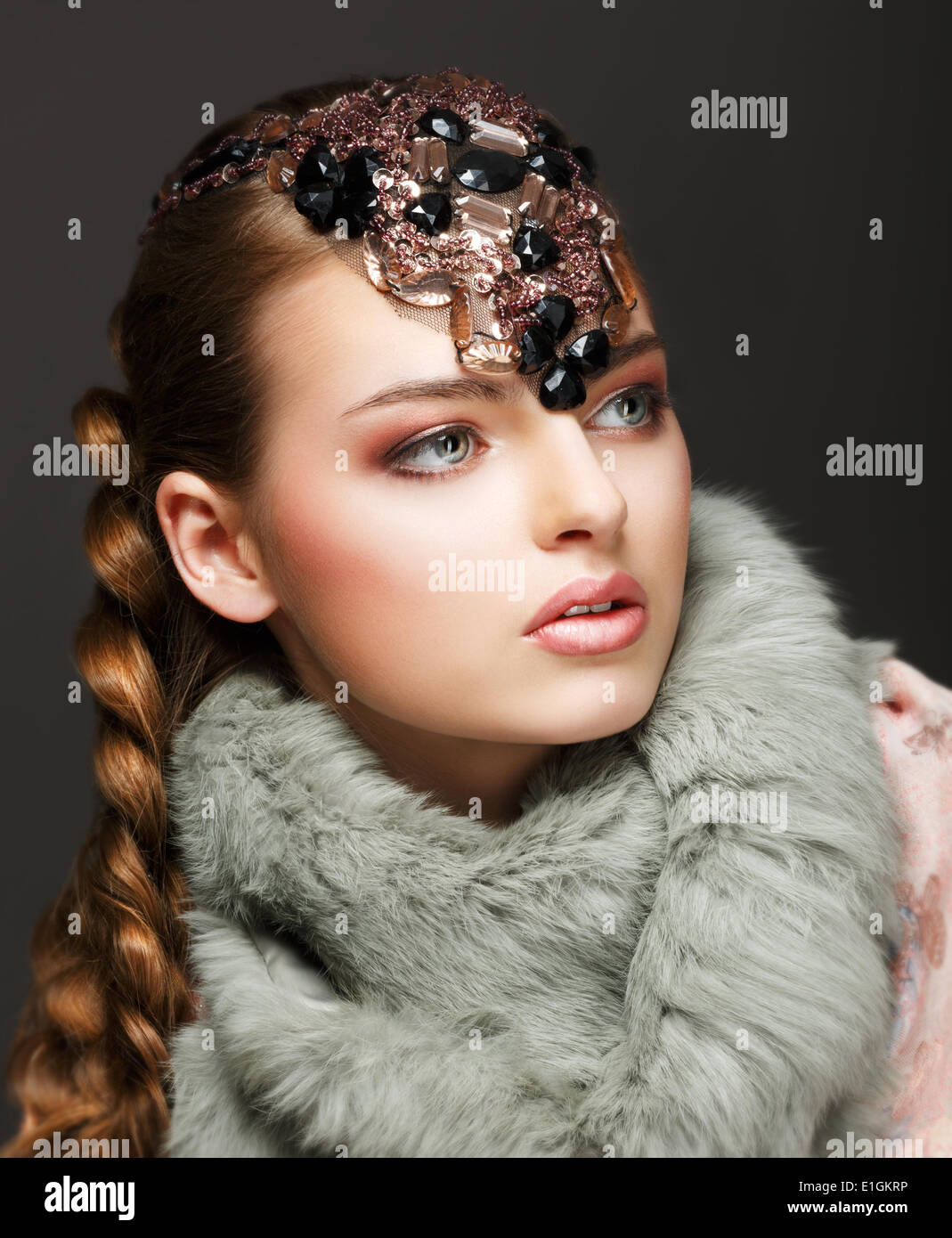 Braided Hair Luxurious Woman in Fur Collar and Gemstones. Jewels - Stock Image
