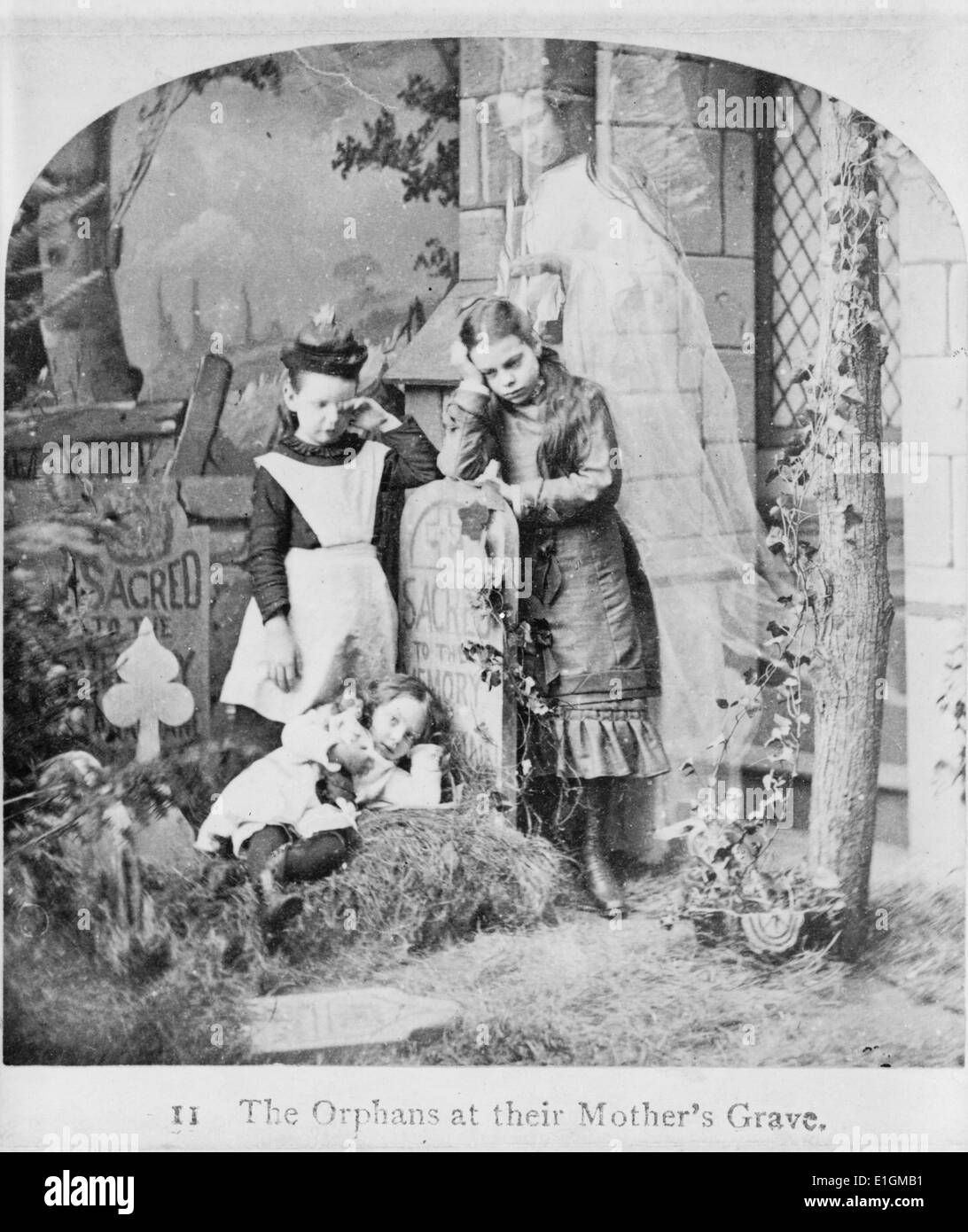 Photographic print of three orphans and the ghost of their mother at her grave. Dated 1889 - Stock Image
