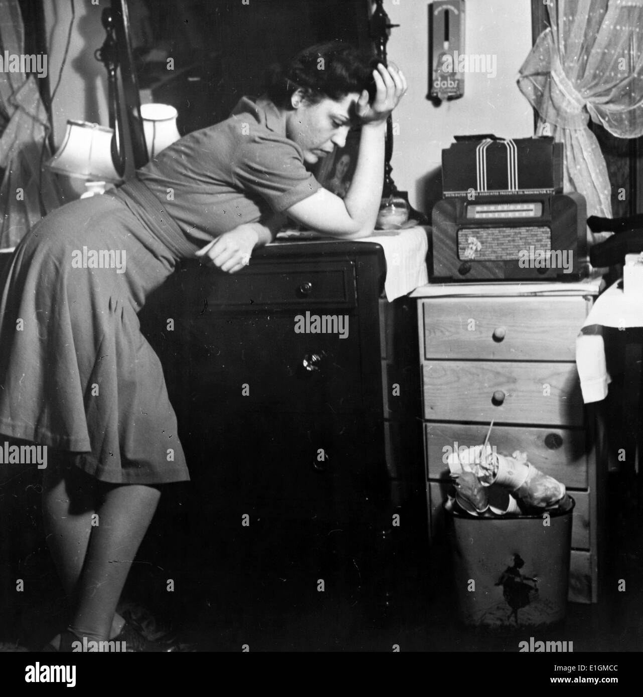 Photograph of a woman listening to a murder mystery on the radio in a boarding house. Dated 1943 Stock Photo