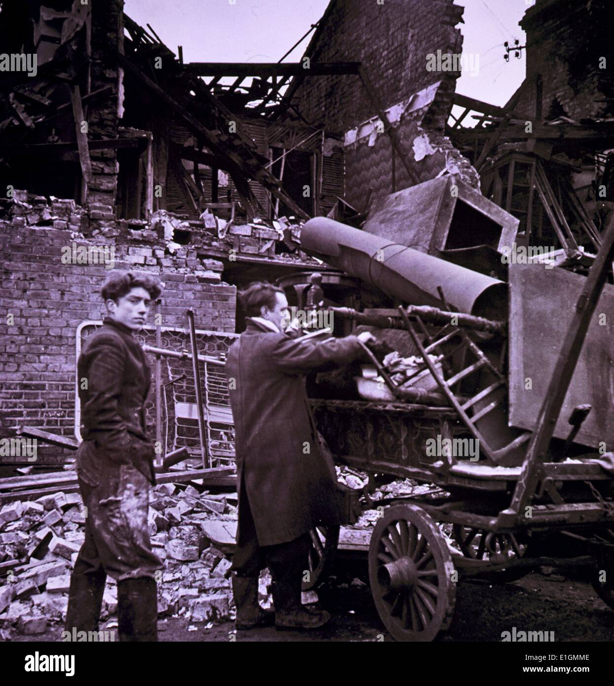 Two men load a wagon with their possessions, among ruins. - Stock Image