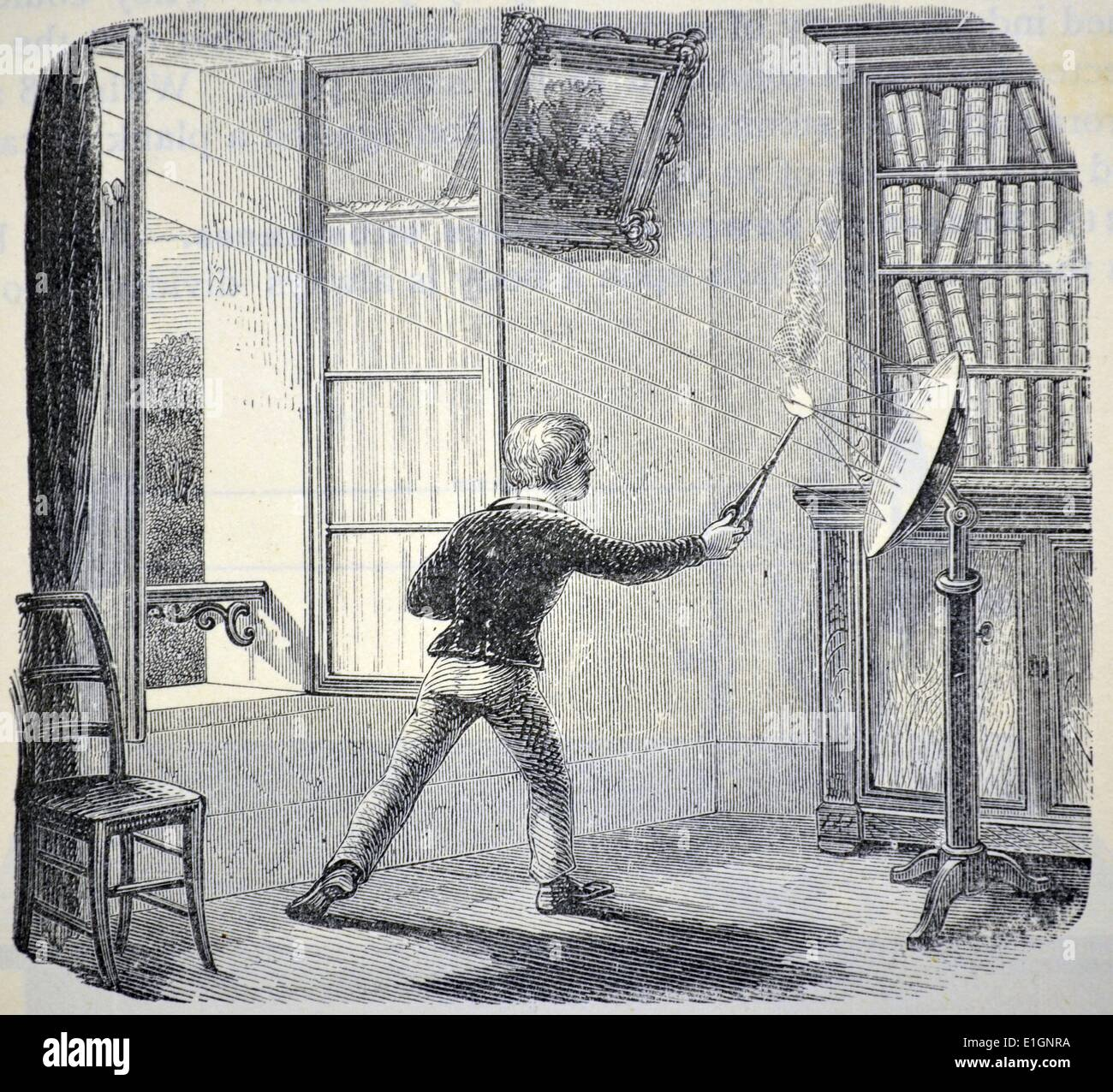 Boy lighting paper using the sun's rays focused by a concave mirror. Engraving from ''Natural Philosophy'' by E. Stock Photo