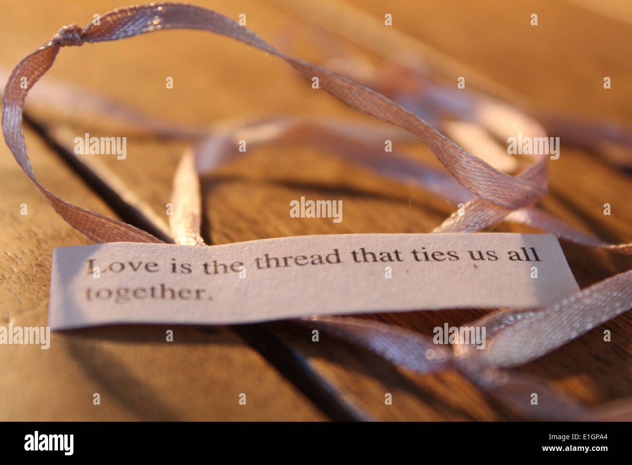 Quote which reads ' love is the thread that ties us together' next to a knotted pink ribbon - Stock Image