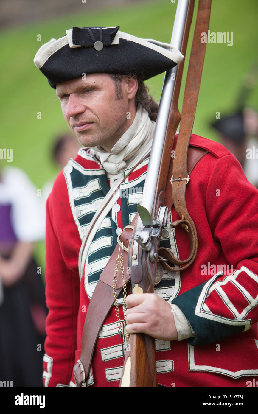 A soldier dressed in traditional 17th Century English Army Redcoat uniform holding shouldered a flintlock musket. - Stock Image