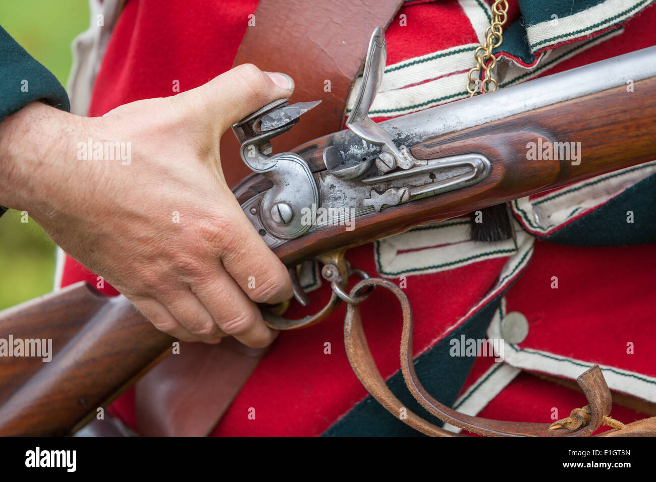 A soldier dressed in traditional 17th Century English Army Redcoat uniform loading a flintlock musket. - Stock Image