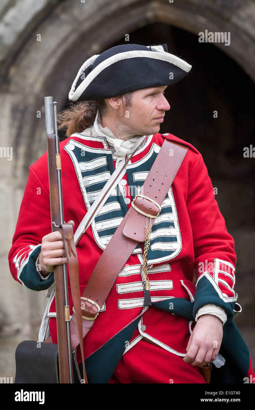 A soldier dressed in traditional 17th Century English Army Redcoat uniform carrying a flintlock musket outside a castle entrance - Stock Image