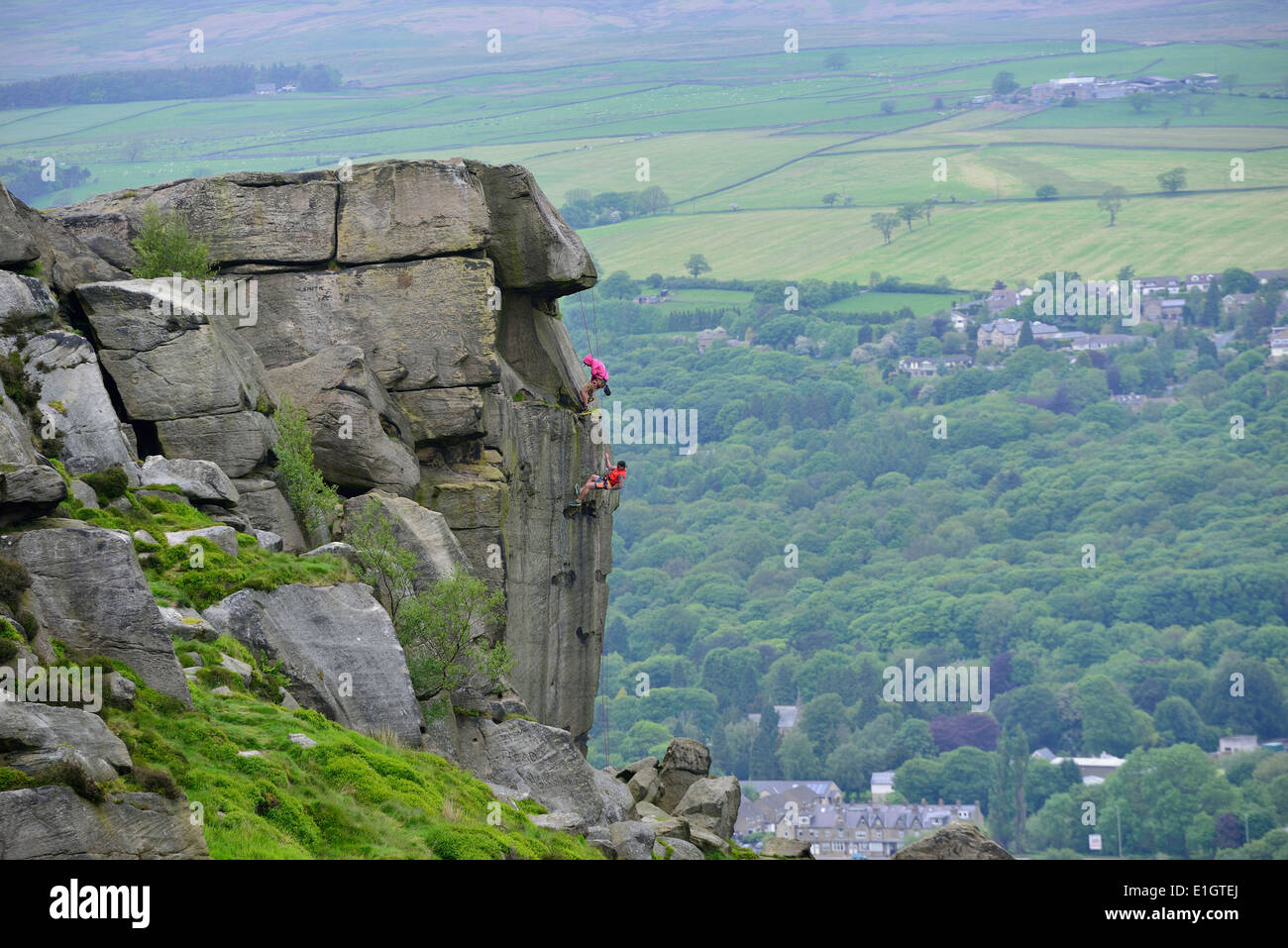 Abseiling down the Cow and Calf rock face on Ilkley Moor West Yorkshire England UK - Stock Image