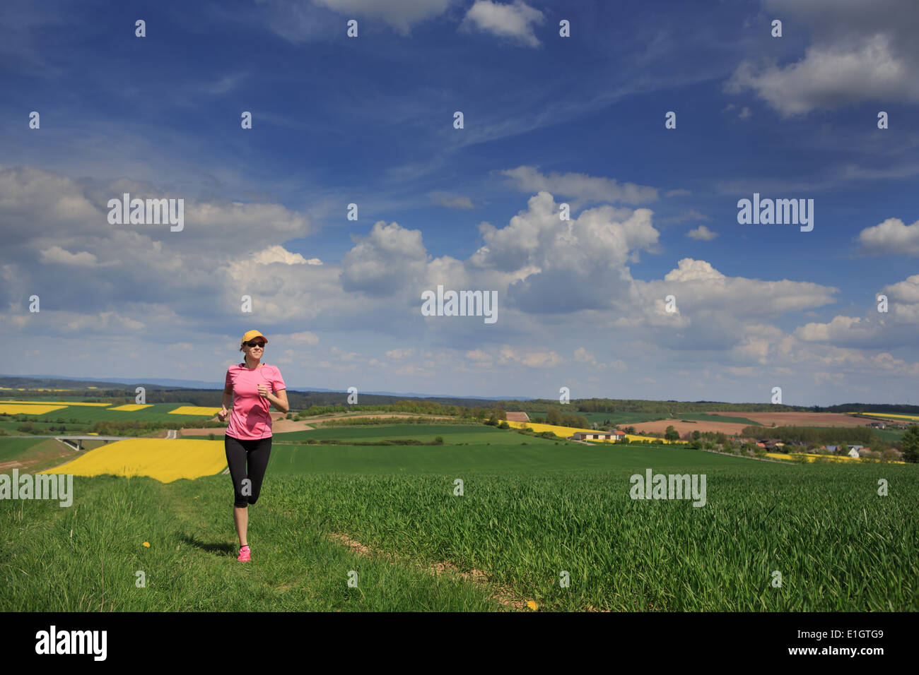 woman jogging through fields at the springtime - Stock Image
