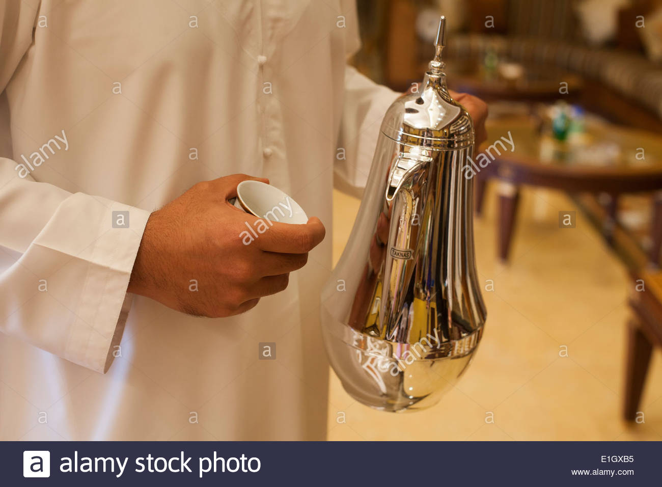 Arab holding a silver coffeepot - Stock Image