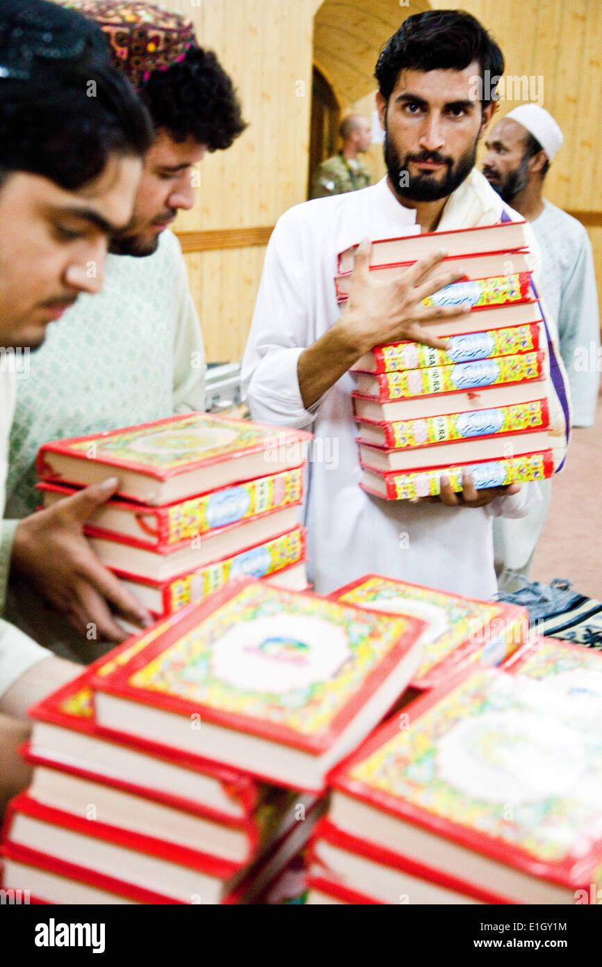 Afghan residents hand out prayer books after a Ramadan feast in Kandahar City, Afghanistan, Aug. 10, 2011. Afghans fast during - Stock Image