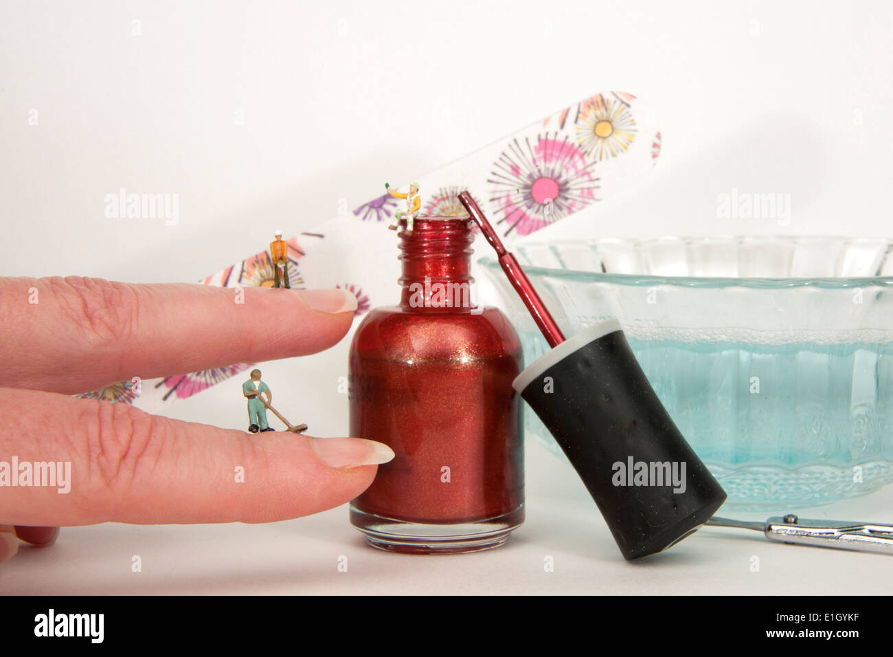 Hand with minature people giving a manicure with nail polish, emery board and soaking bowl in background. - Stock Image