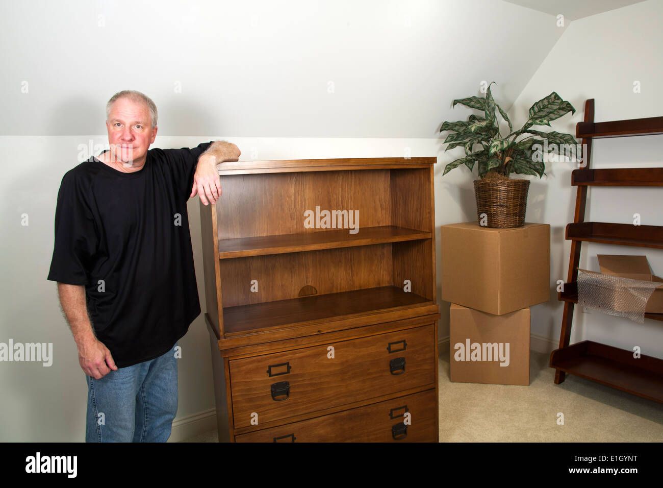 Man standing next to bare furniture and moving boxes in his new home - Stock Image