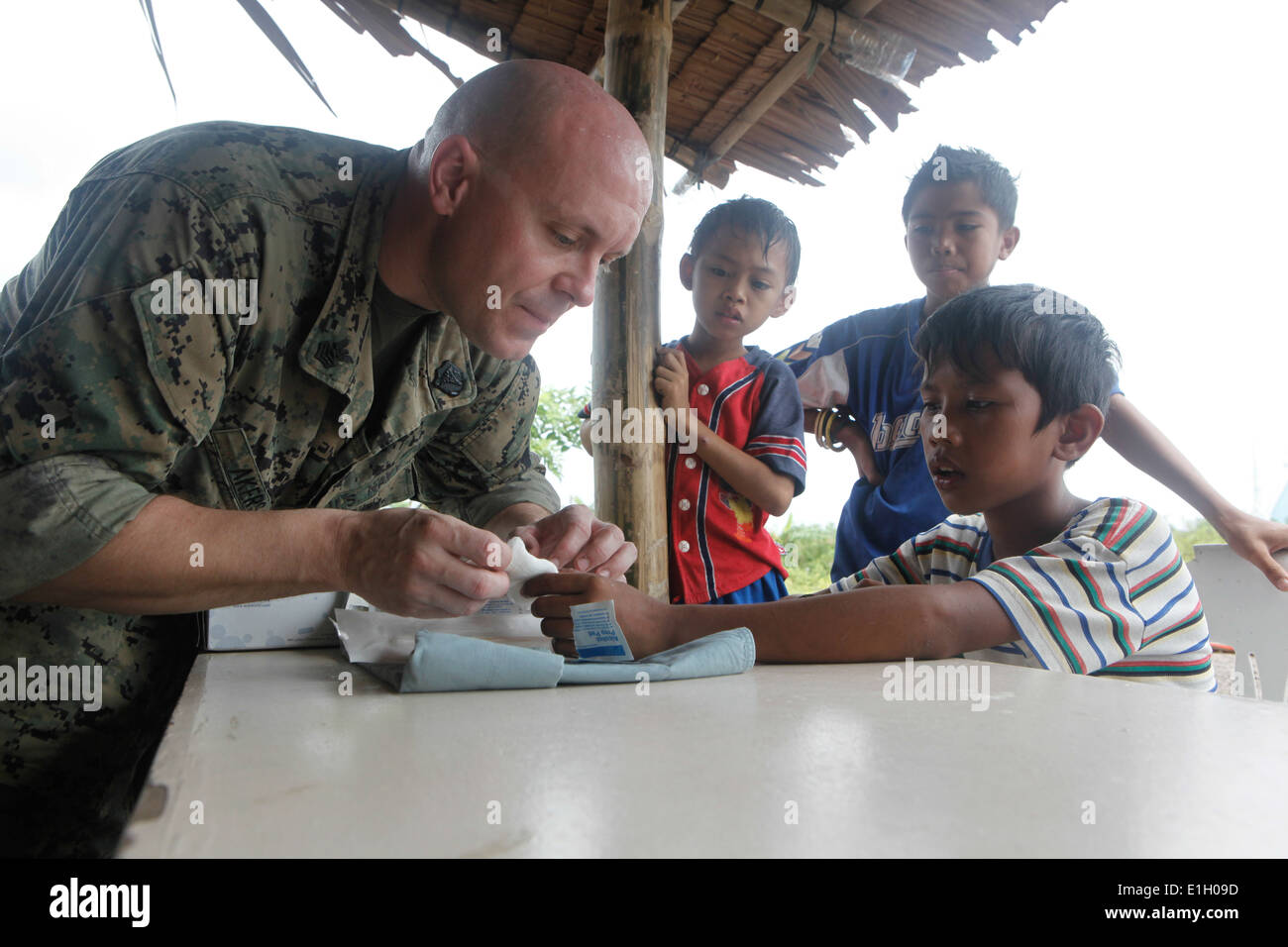 U.S. Navy Hospital Corpsman 1st Class Johnathan Akers, left, performs a medical procedure on a Filipino boy?s hand Oct. 9, 2011 - Stock Image