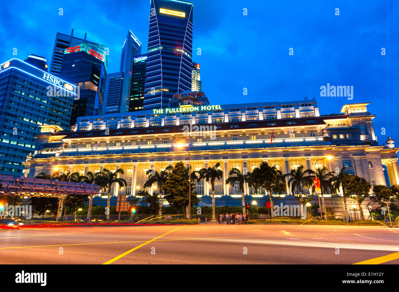 The Fullerton Hotel lit up in early evening in Singapore. - Stock Image