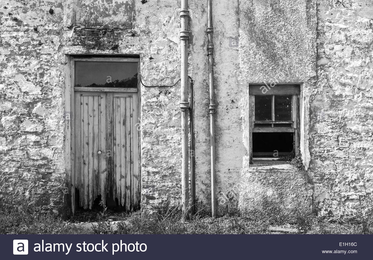 Derelict Scottish farmhouse, whitewash, flat front view of door and open window - Stock Image