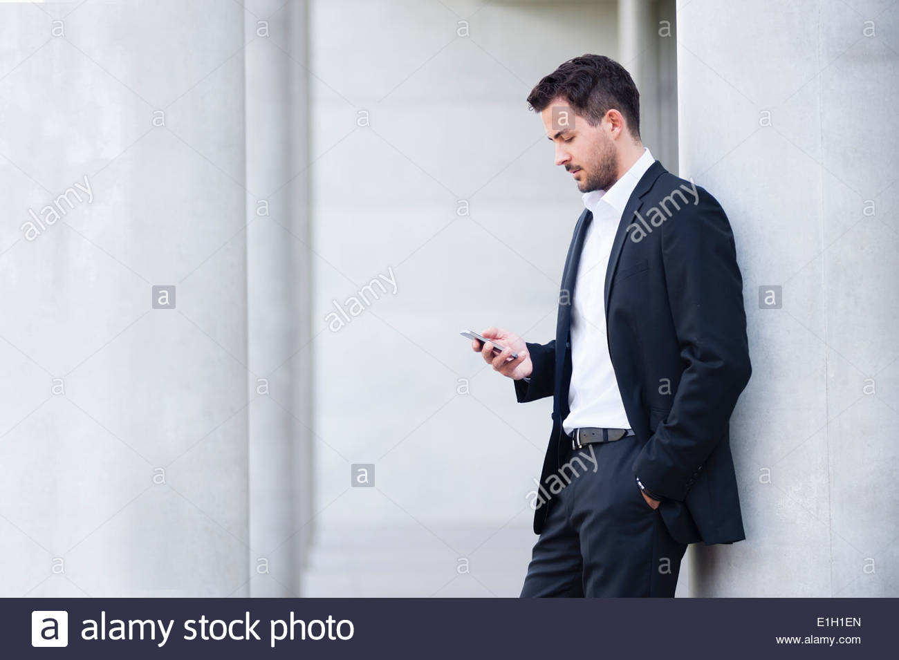 Young businessman leaning against wall reading texts on smartphone - Stock Image