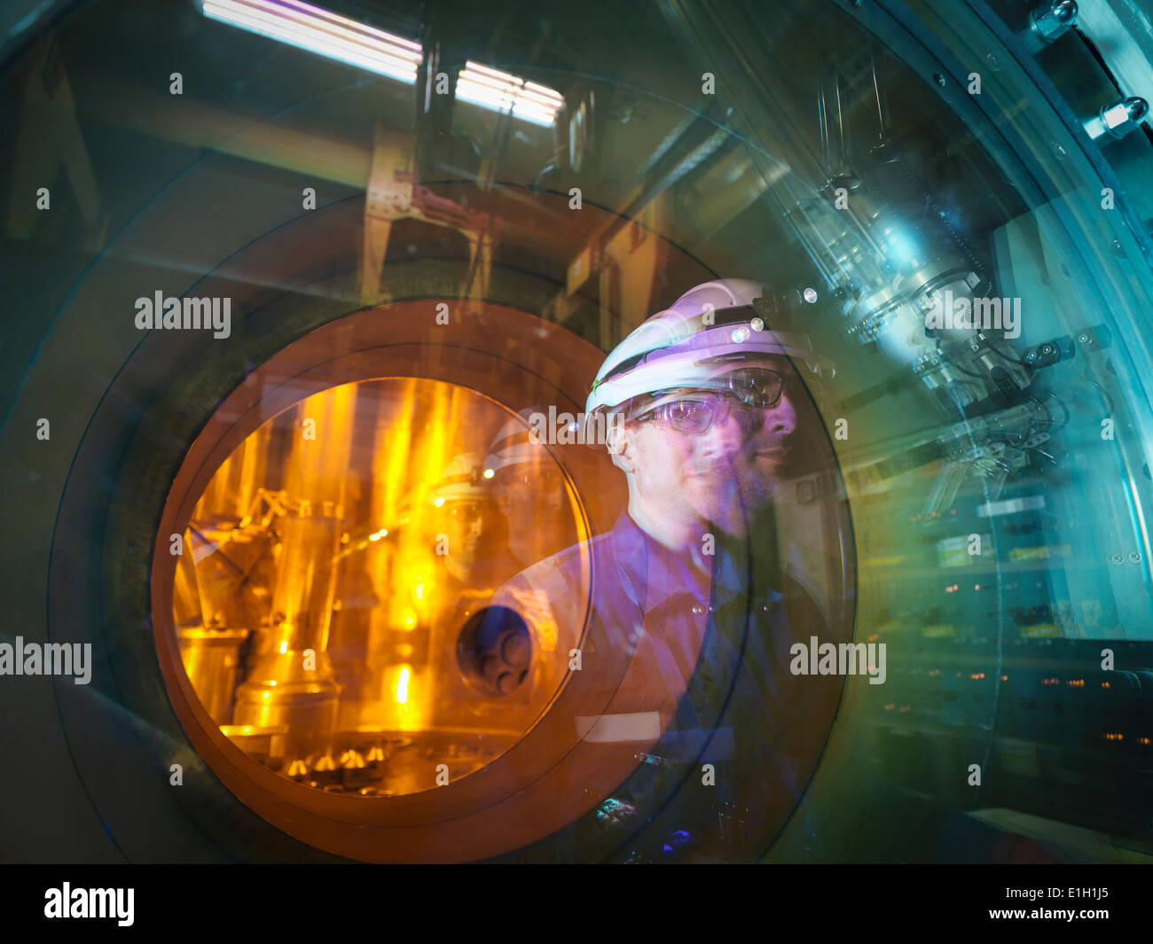 Engineer reflected in glass of fuel rod handling machine in nuclear power station - Stock Image