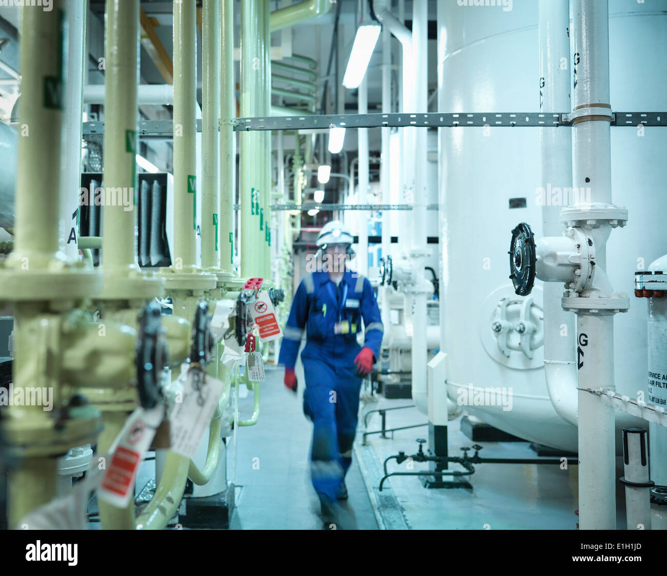 Engineer walking amongst pipes of nuclear power station Stock Photo