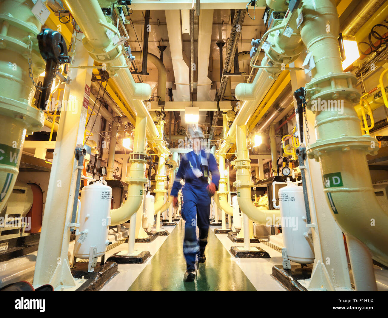 Engineer walking amongst pipes of nuclear power station - Stock Image