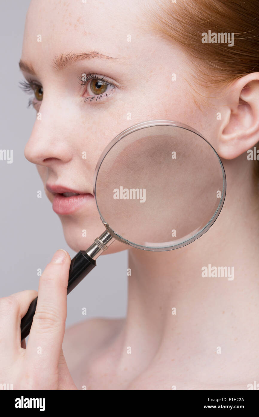 Portrait of young woman, magnifying glass on cheek - Stock Image