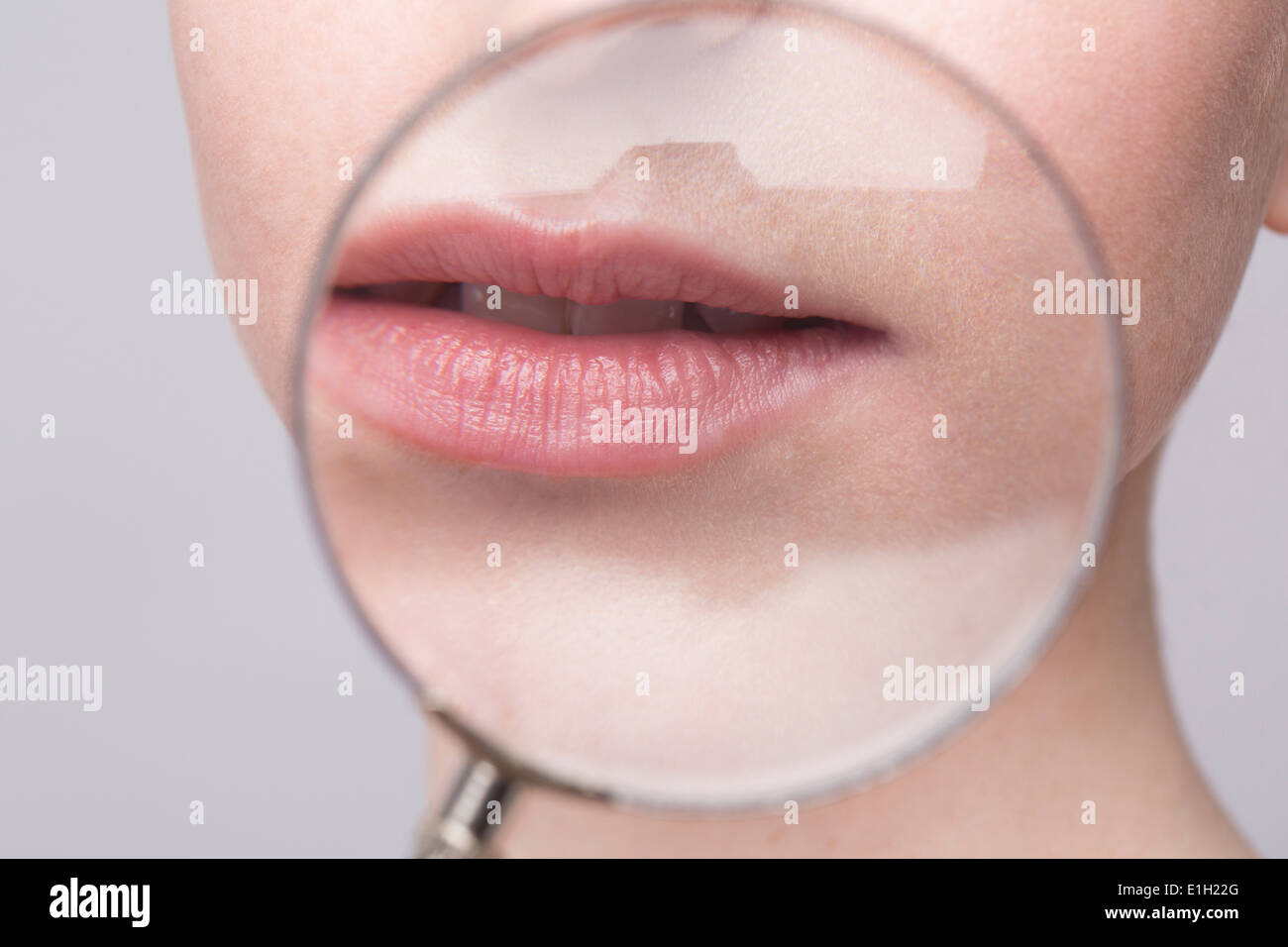 Portrait of young woman, magnifying glass on mouth - Stock Image