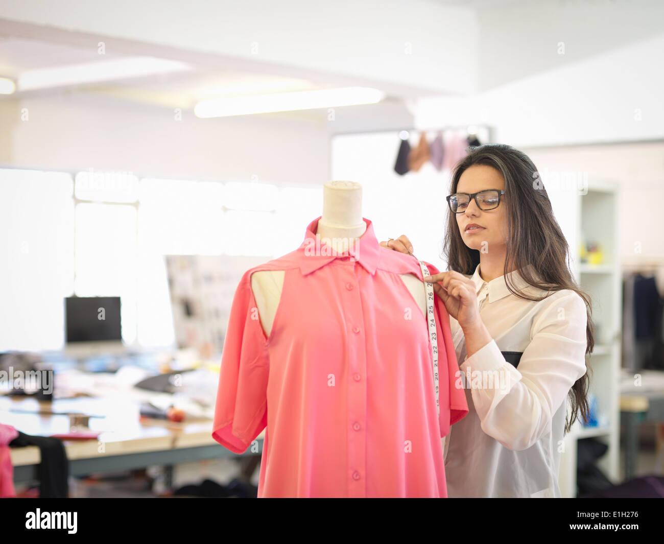 Fashion designer measuring garment in fashion design studio - Stock Image
