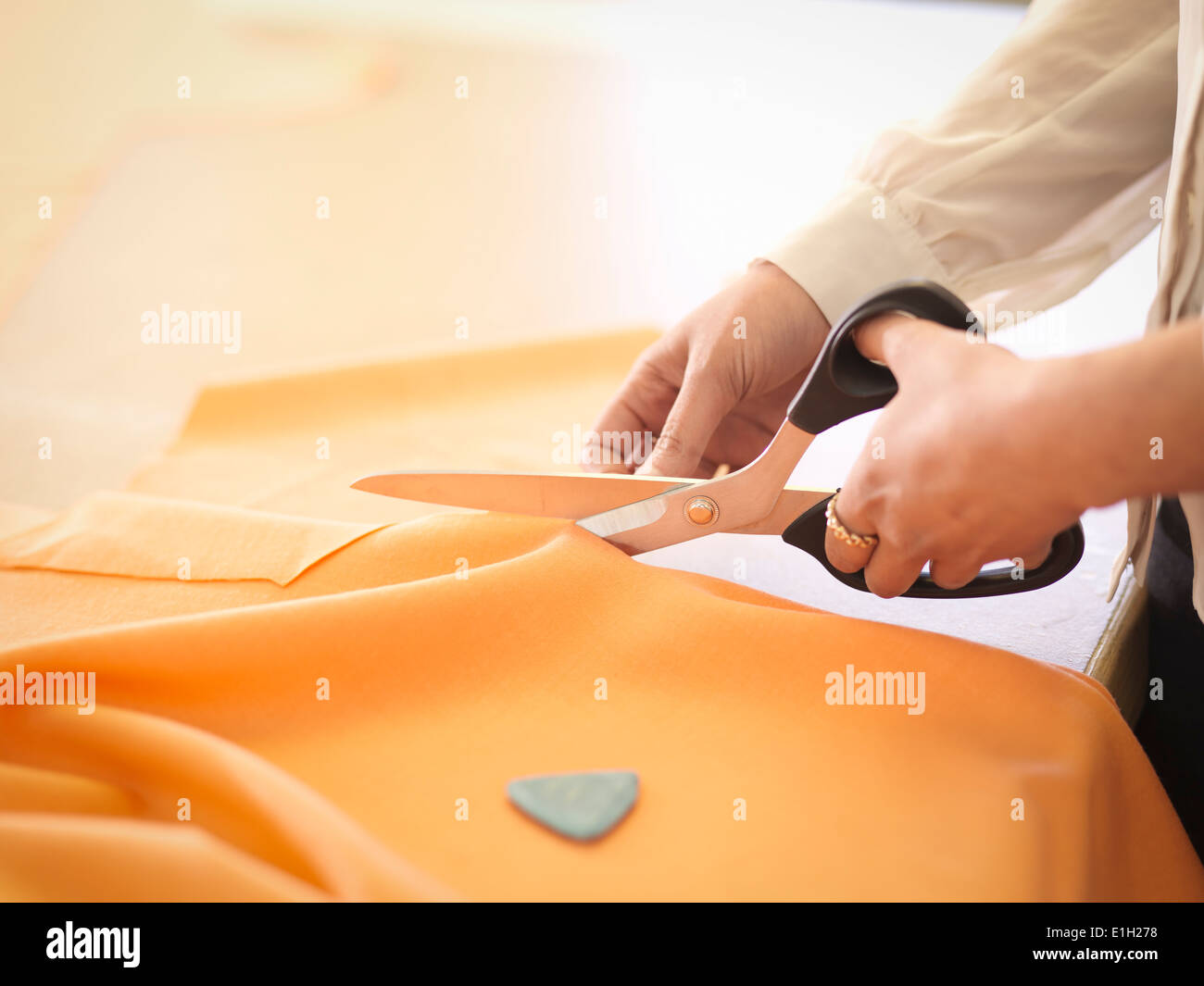 Fashion designer cutting cloth in fashion design studio, close up - Stock Image