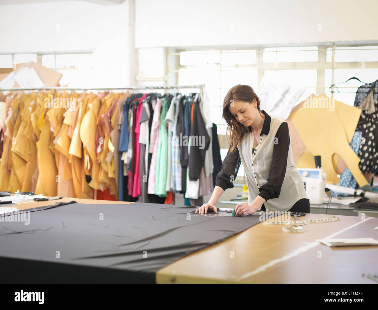 Fashion designer measuring fabric in fashion design studio - Stock Image