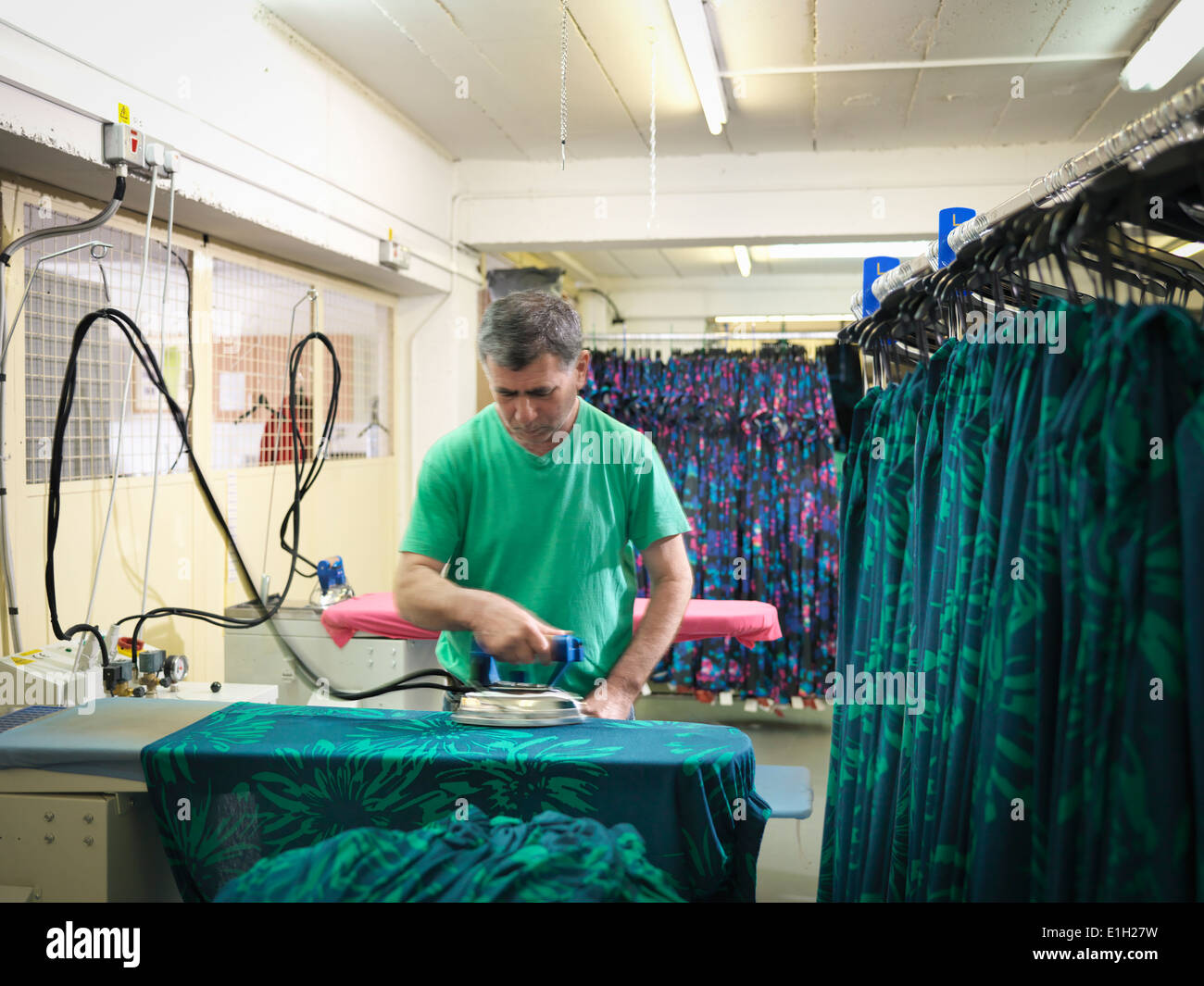 Garment worker ironing clothing in clothing factory - Stock Image