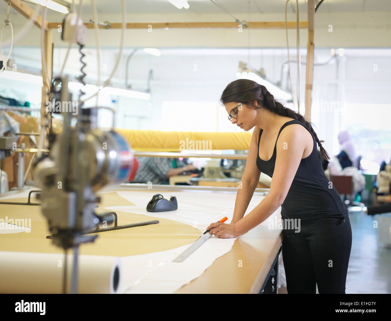 Female garment worker marking cloth in clothing factory - Stock Image