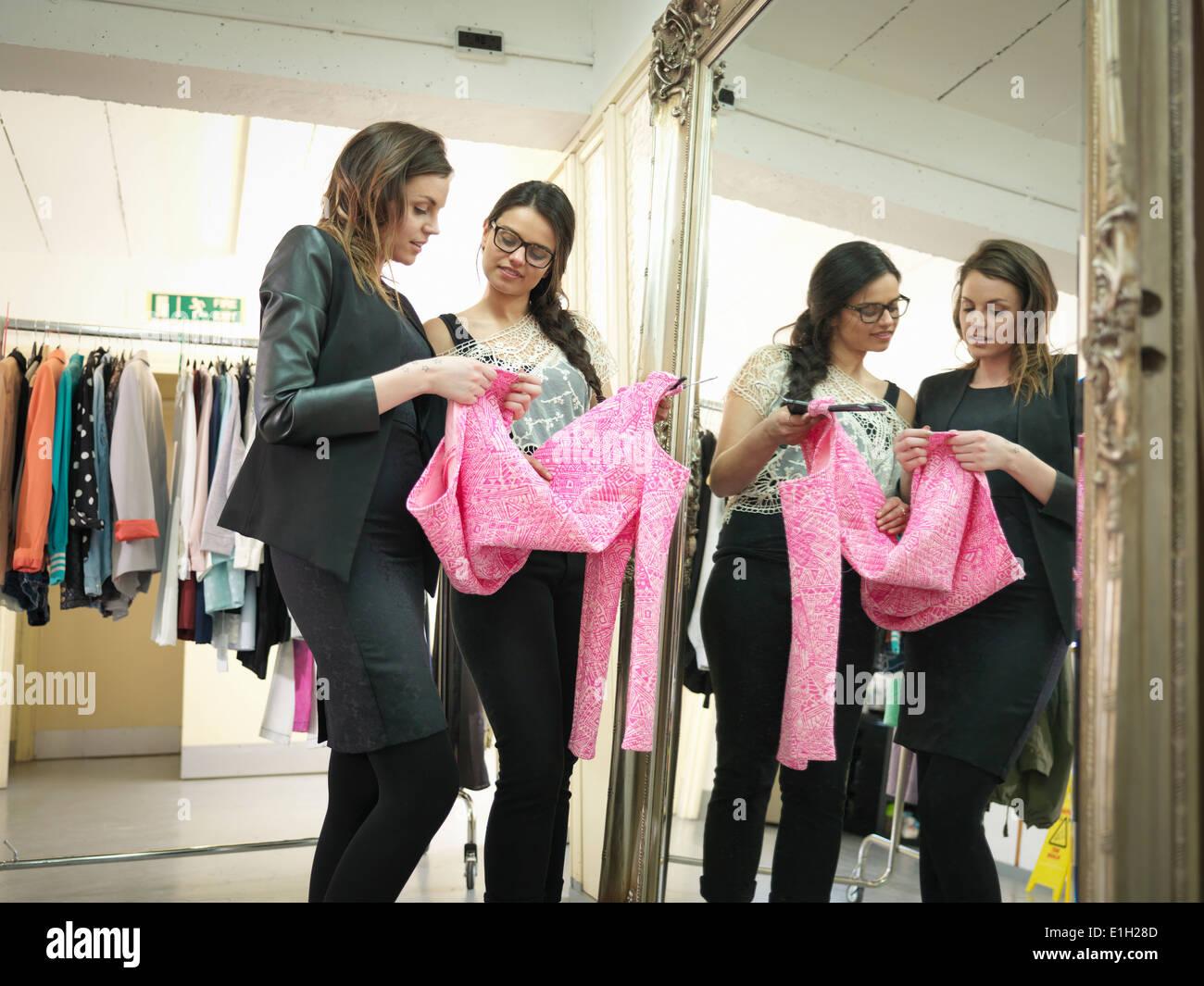 Fashion designers check garment in fashion design studio - Stock Image