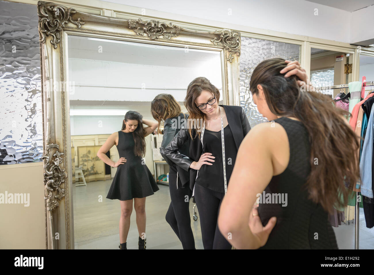 Fashion designers working together on dress in fashion studio - Stock Image