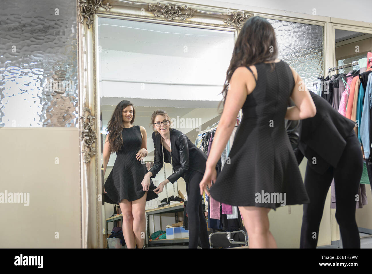 Fashion designers working together in front of mirror in fashion studio - Stock Image