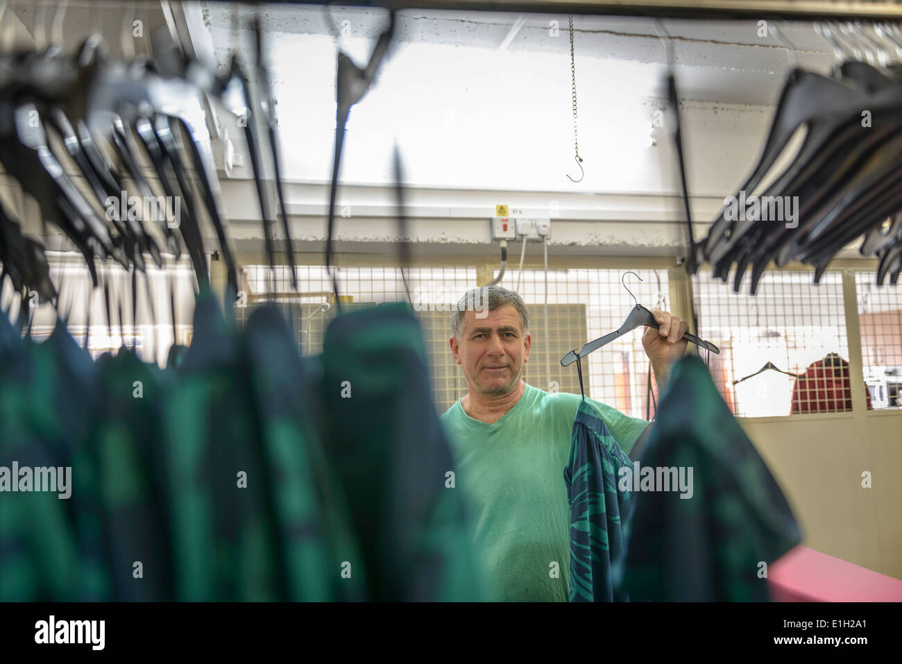 Worker hanging garments in clothing factory - Stock Image