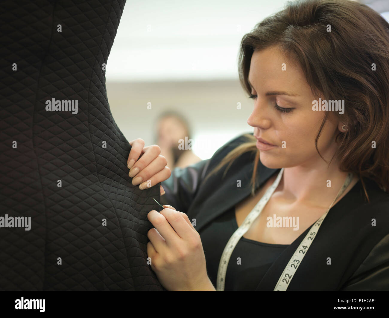 Fashion designer adjusting garment in fashion design studio - Stock Image