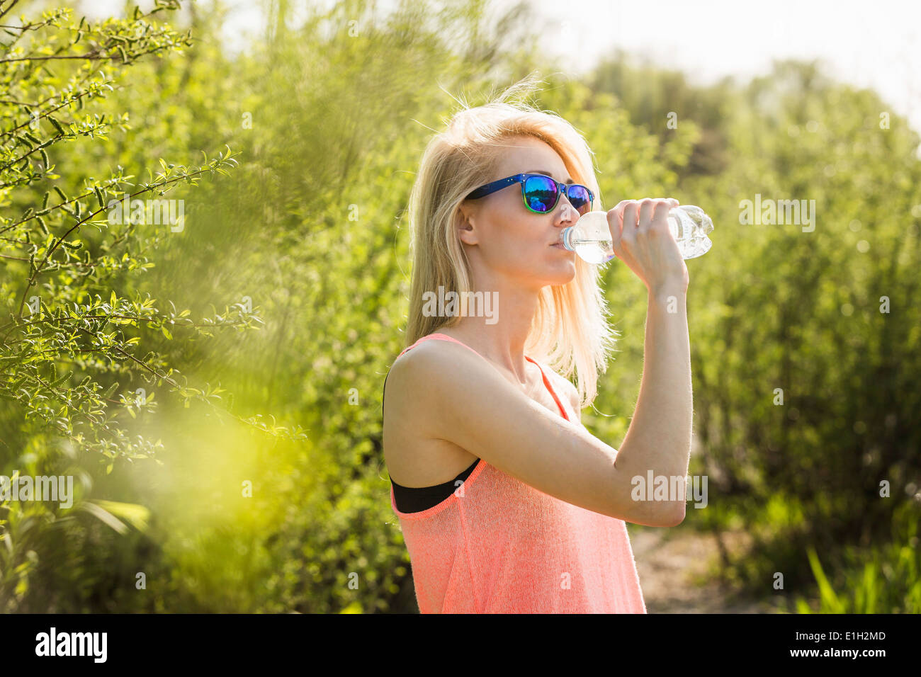 Young woman in park drinking bottle of water - Stock Image