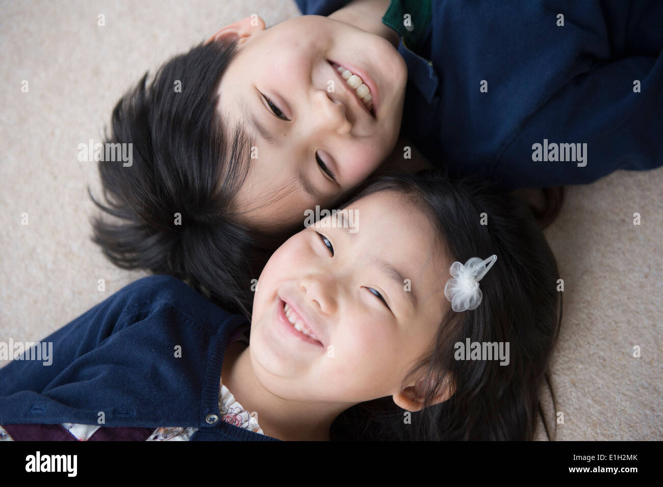 Portrait of brother and sister lying on carpet - Stock Image