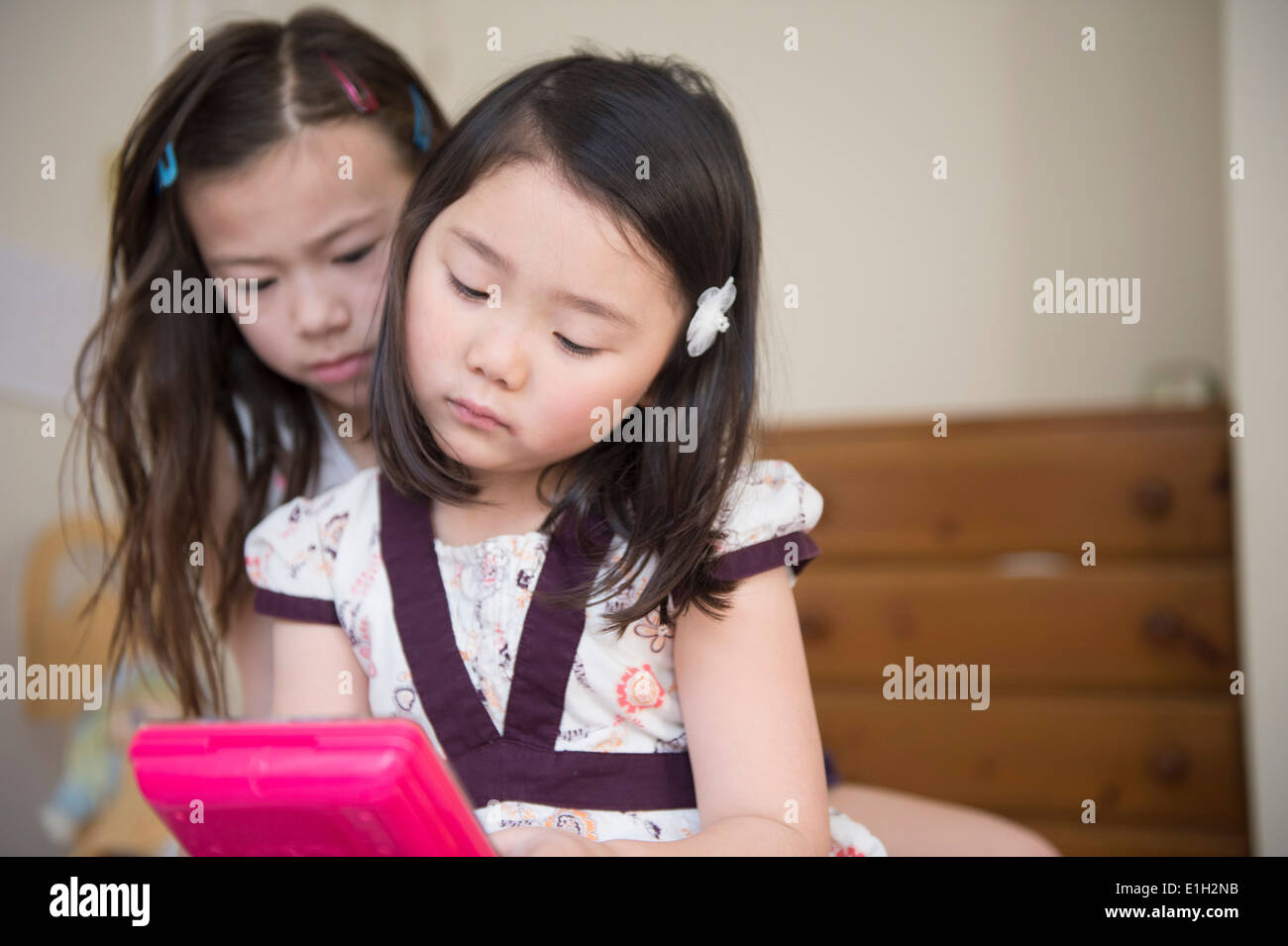 Two young female friends unhappy with one computer game - Stock Image