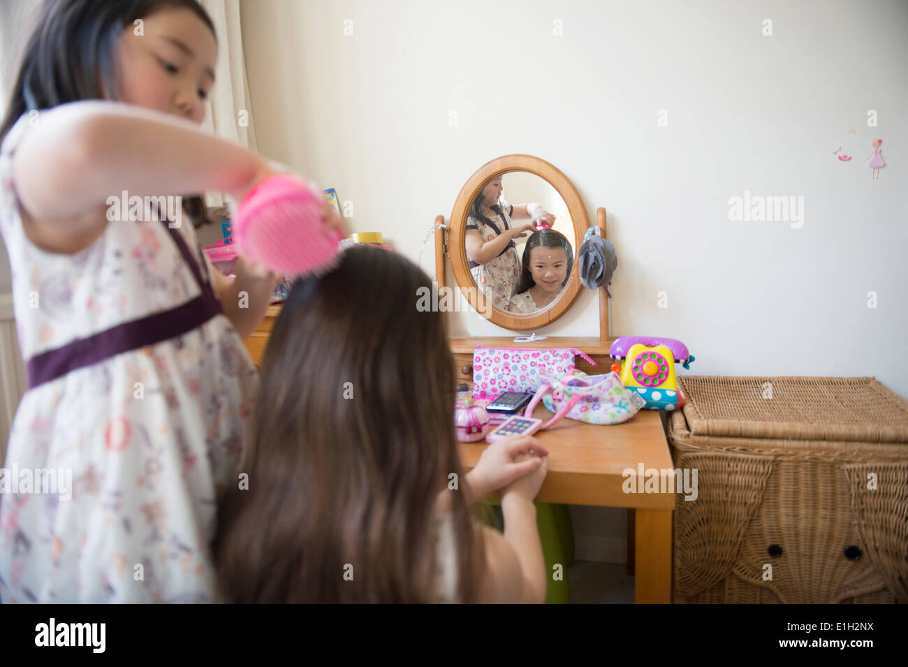 Young girl brushing friends hair in bedroom - Stock Image