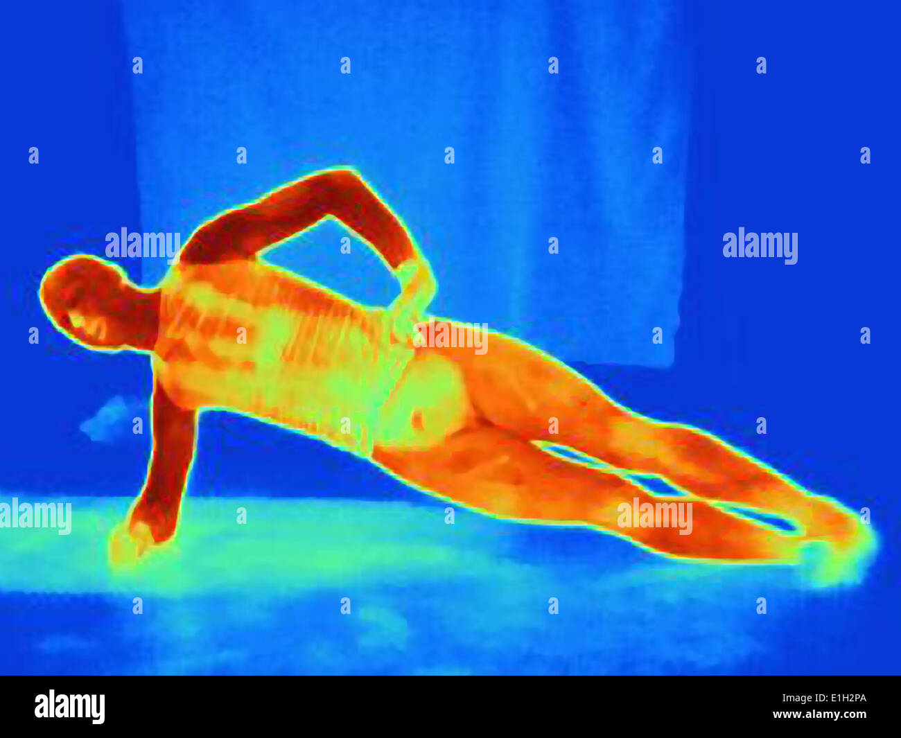 Thermal image of young man doing one arm push ups. The image shows the heat produced by the muscles - Stock Image