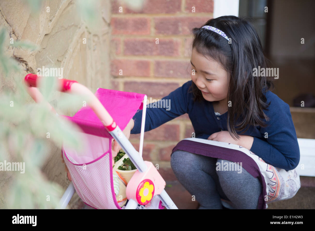 Young girl playing with toy pushchair - Stock Image
