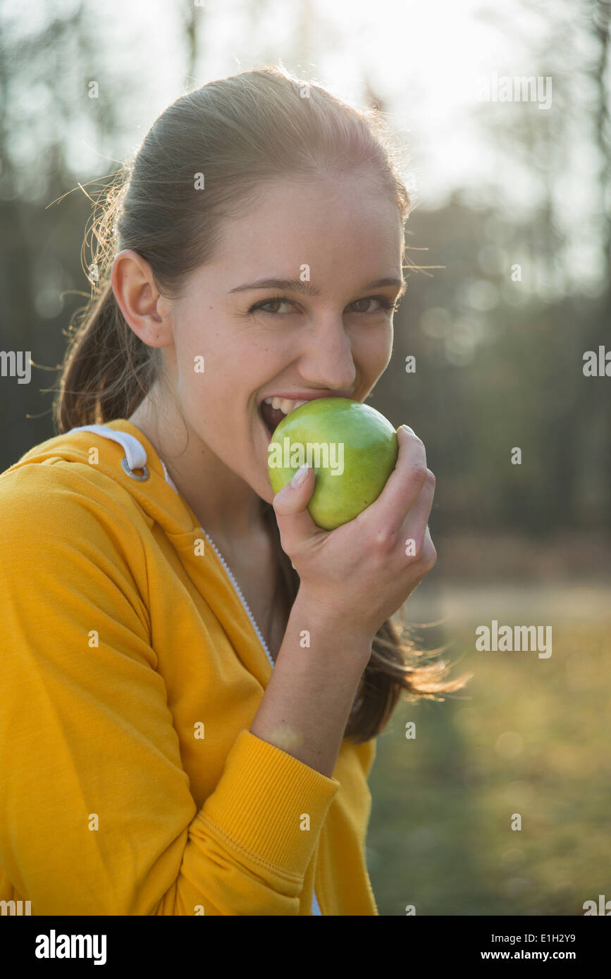 Portrait of young female runner eating an apple - Stock Image
