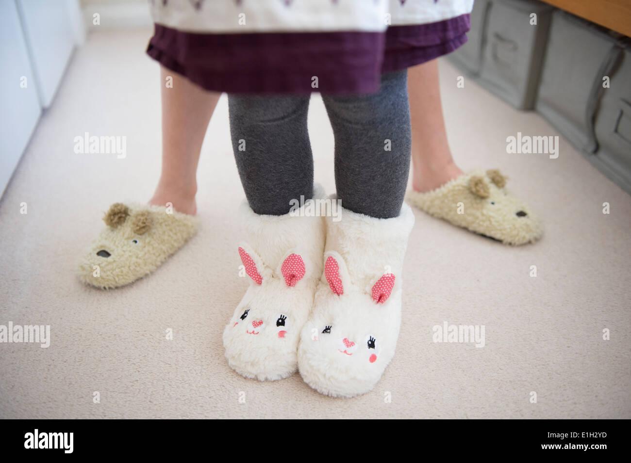Children wearing animal slippers - Stock Image