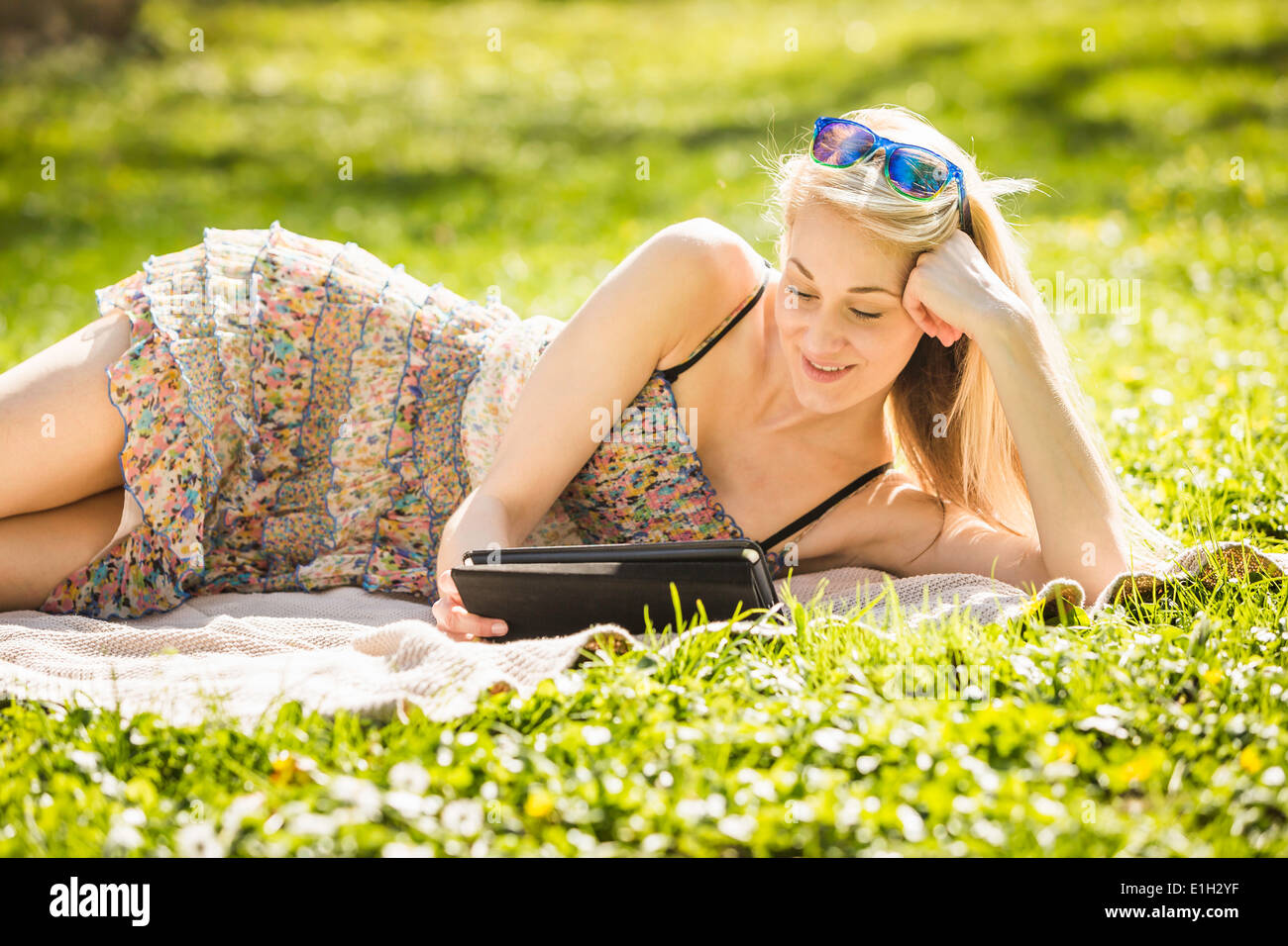 Young woman lying in forest looking at digital tablet - Stock Image