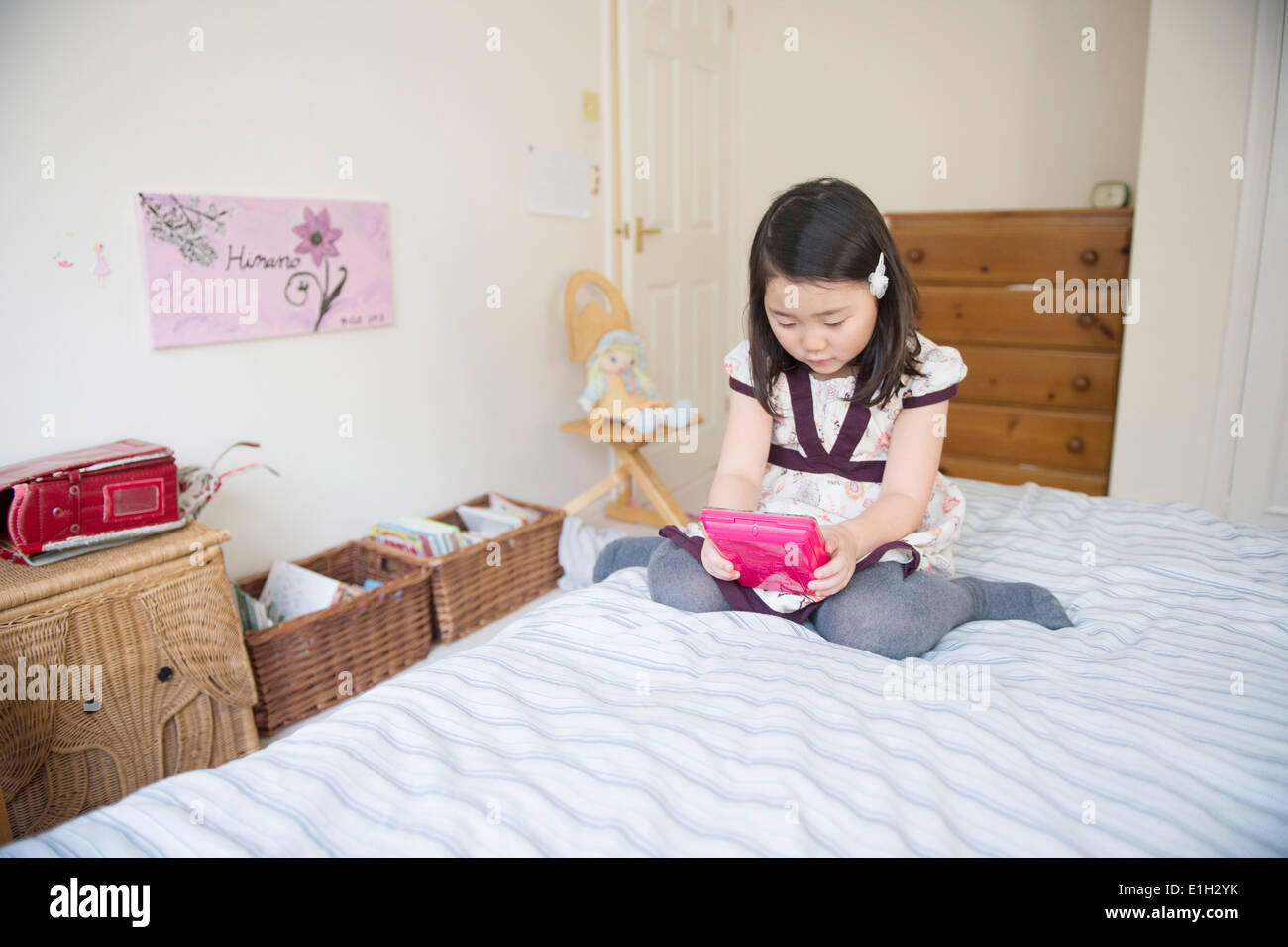 Young girl sitting on bed playing computer game - Stock Image