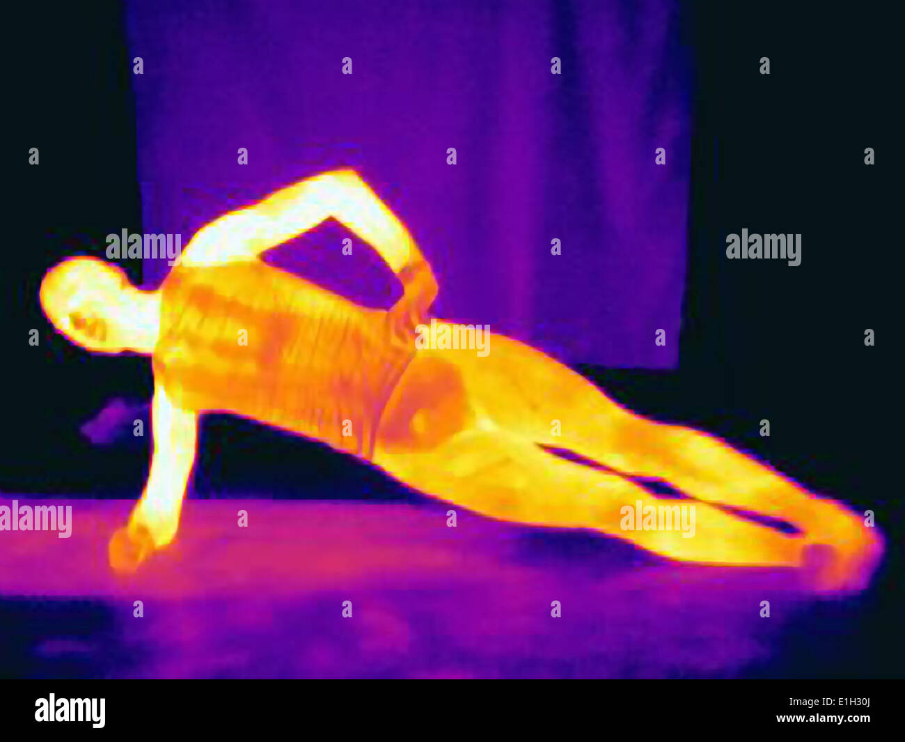 Thermal image of young male athlete doing one arm push ups. The image shows the heat produced by the muscles - Stock Image